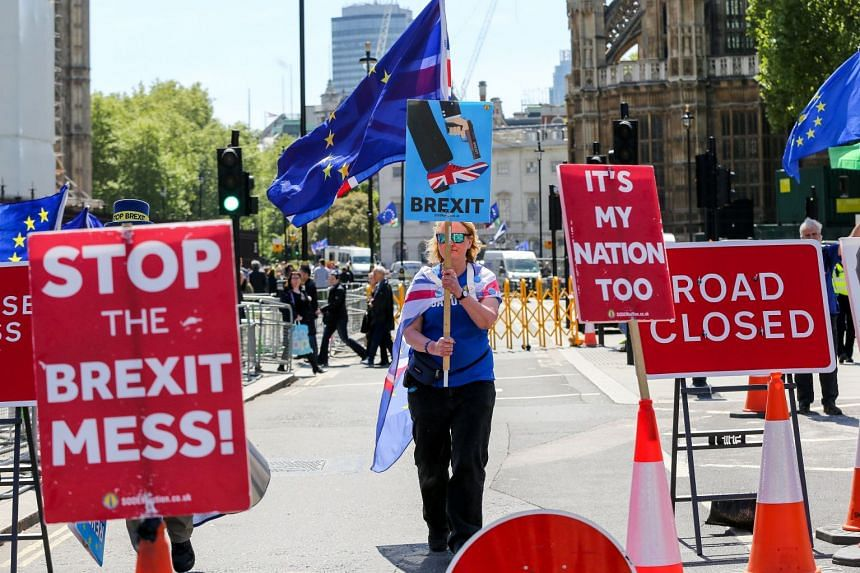 An anti-Brexit demonstrators holds a placard during a protest outside the Houses of Parliament on May 14, 2019.