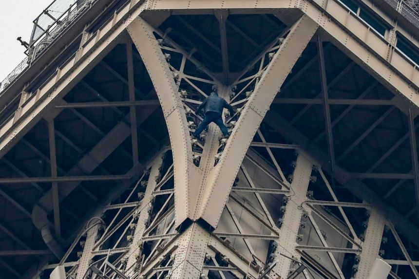 A man (above, centre) climbs up to the top of the Eiffel Tower in Paris, without any protection, on May 20, 2019. The Eiffel Tower was evacuated in the afternoon after he was spotted climbing up the Paris landmark, the company that operates the struc