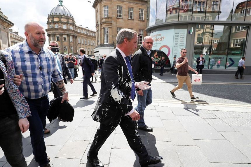 Brexit Party leader Nigel Farage gestures after being hit with a milkshake while arriving for a Brexit Party campaign event in Newcastle, Britain, May 20, 2019.