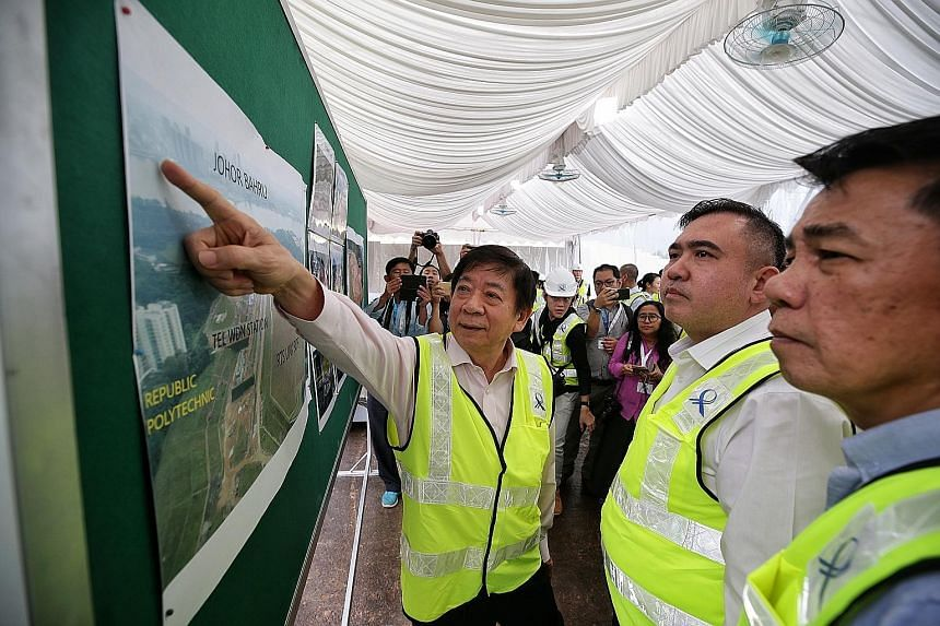 (From left) Transport Minister Khaw Boon Wan, his Malaysian counterpart Anthony Loke and Datuk Mohd Khairul Adib Abdul Rahman, secretary-general of Malaysia's Transport Ministry, looking at an aerial shot of the RTS Link site in Woodlands North yeste
