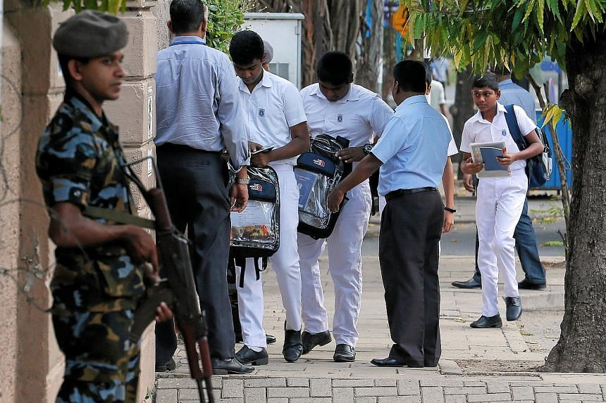 A Sri Lankan soldier on guard at the entrance to St Joseph's school as staff search students' bags. Catholic schools reopened yesterday, a month after the deadly Easter Sunday bombings in Colombo.