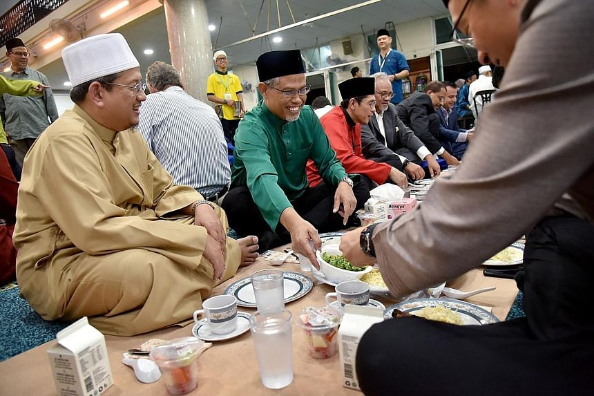 Members and leaders of the Muslim community with Minister in-charge of Muslim Affairs Masagos Zulkifli (in green shirt) having a meal of mandi rice after breaking fast yesterday at the Masjid Al-Istiqamah in Serangoon. Mr Masagos, who is also the Min
