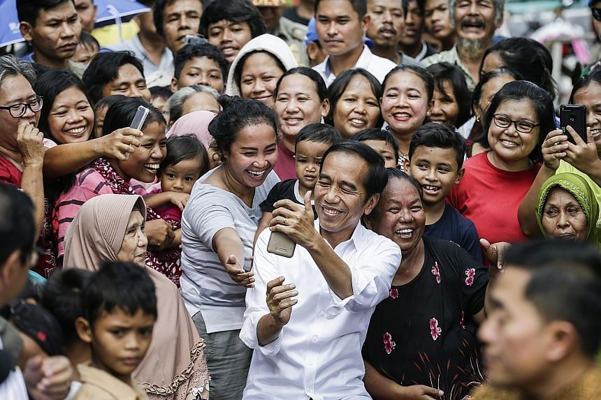 President Joko Widodo taking photographs with residents of a slum area in Jakarta following his victory speech yesterday, in which he pledged to be a leader and protector of all Indonesians.