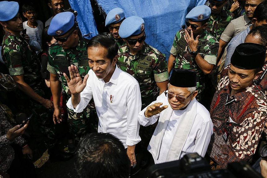Above: Indonesian President Joko Widodo (left) and his running mate Ma'ruf Amin greeting residents after a victory speech in a Jakarta slum area yesterday. Right: Defeated presidential candidate Prabowo Subianto (at left) and his running mate Sandiag