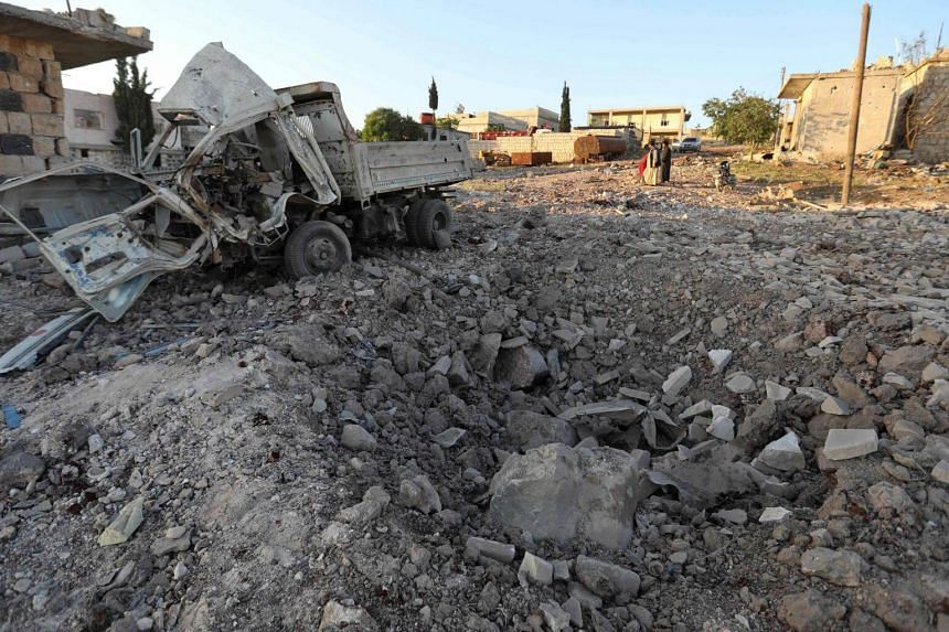 A damaged vehicle lies next to a crater cased by reported airstrikes by the Syrian regime ally Russia, in the town of Kafranbel in the rebel-held part of the Syrian Idlib province, on May 20, 2019.