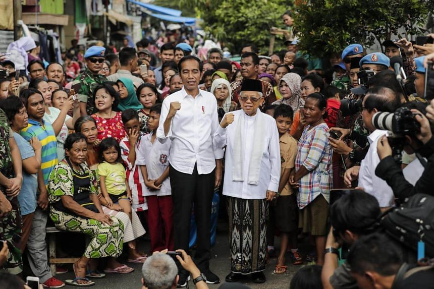 Indonesia's incumbent President from the Indonesian Democratic Party of Struggle Joko Widodo (centre left) and his running mate Ma'ruf Amin (centre right) pose for photographs after delivering their victory speech in Jakarta, on May 21, 2019.