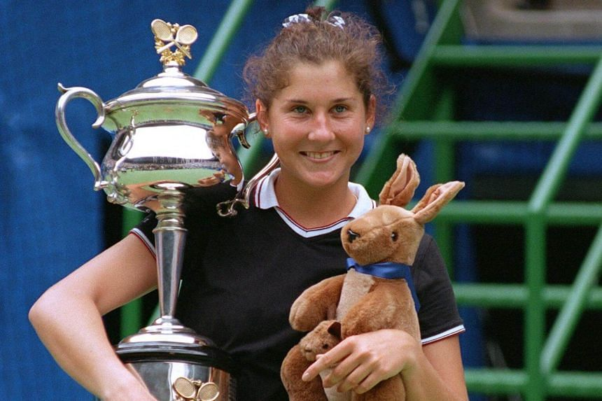 Tennis player Monica Seles holds the Winner's trophy and a toy kangaroo after defeating German Anke Huber in the Women's Australian Open final on Jan 27, 1996.