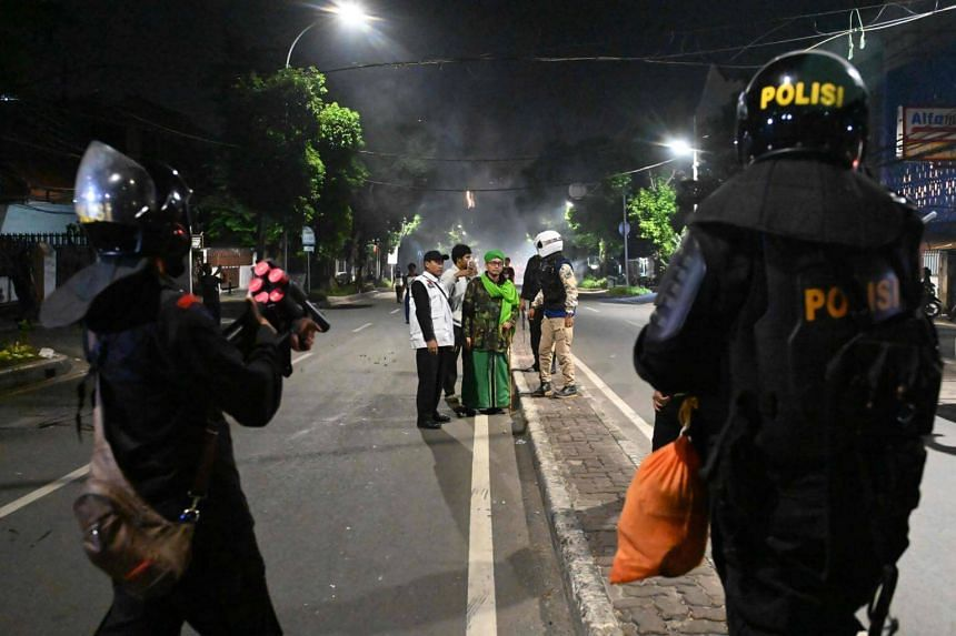 Indonesian police prepare tear gas launchers to disperse protesters during a demonstration outside the Elections Oversight Body in Jakarta on May 22, 2019.