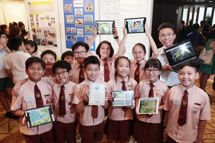 The 11 students from Temasek Primary School with their teacher, Mr Lim Wu Yi, posing with tablets and laptops showcasing their project, Symbiosis.