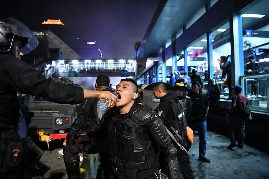 A policeman drinking water during clashes with protesters in Sarinah, central Jakarta, on May 22, 2019, following the release of the April 17 presidential election results.