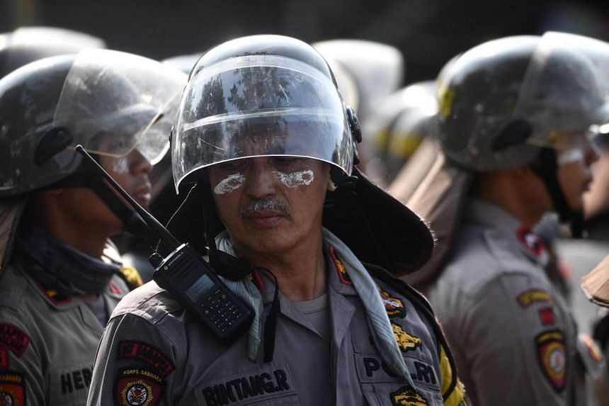 A police officer with toothpaste under his eyes to help with the tear gas irritation, in Jakarta, on May 22, 2019.