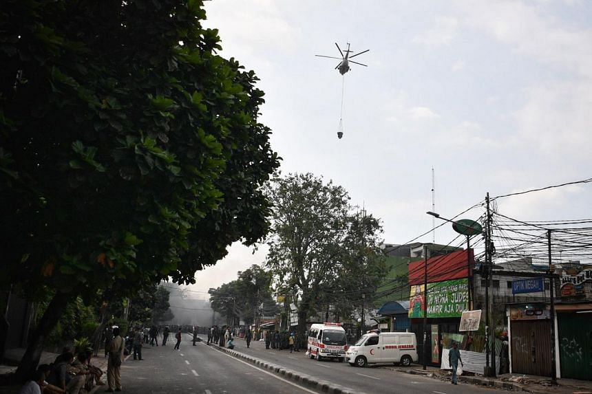 A helicopter deployed to put out fire at Pertamburan, Jakarta, where rioters started burning items.