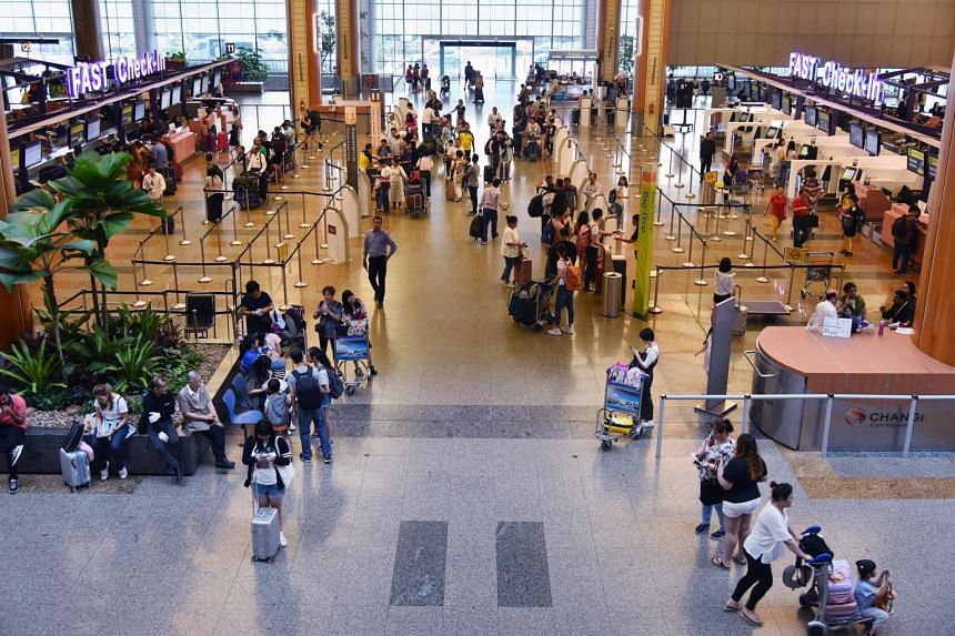 Travellers doing their check-in at the counters in Changi Airport's departure hall.