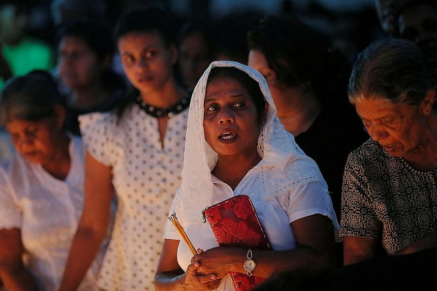 Devotees pray at a remembrance service for the bombing victims at St Sebastian church in Negombo, Sri Lanka, on Tuesday. PHOTO: REUTERS