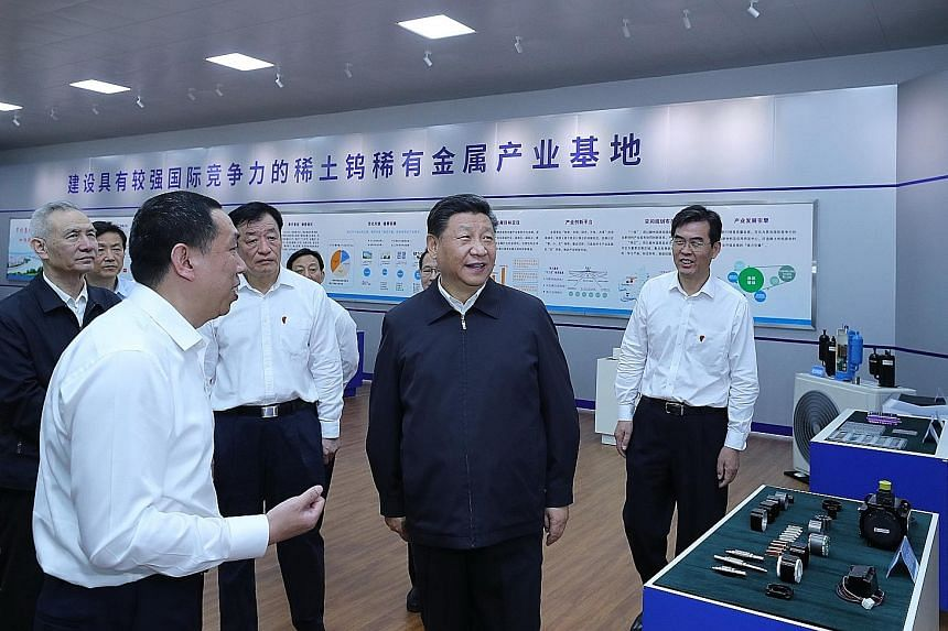 Chinese President Xi Jinping (centre), with Vice-Premier Liu He (far left, wearing black jacket), on a visit to a manufacturer of magnetic materials made of the neodymium rare earth in Ganzhou, Jiangxi province, on Monday.