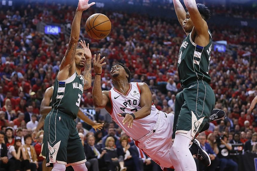 Raptors guard Kyle Lowry taking a shot as Bucks guard George Hill (left) and forward Giannis Antetokounmpo defended in Game 4 of the Eastern Conference finals at Scotiabank Arena in Toronto on Tuesday. The home team won 120-102 to tie the series. PHO