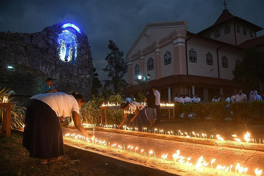 Sri Lankan Christian devotees lighting candles outside St Sebastian's Church in Negombo on Tuesday, a month after the attacks on churches and hotels on Easter Sunday that killed 258 people and wounded nearly 500. The Islamic State in Iraq and Syria c