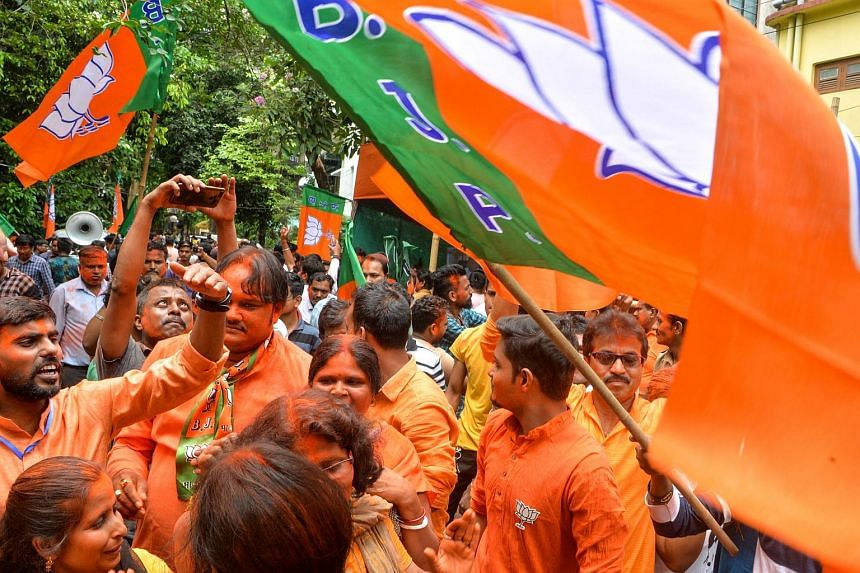 Indian supporters of Bharatiya Janata Party shout slogans and hold party flags as they celebrate on the vote results day for India's general election in Siliguri on May 23, 2019.