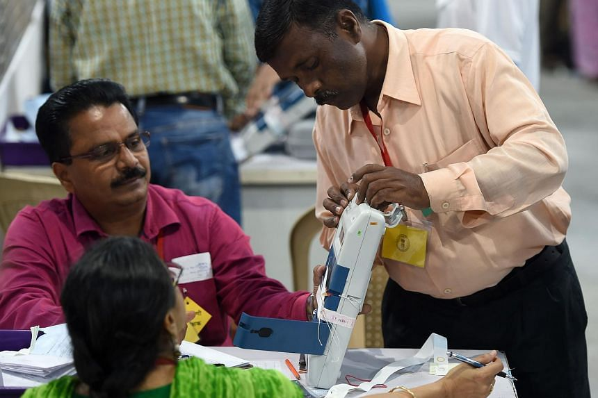 Indian officials inspect an Electronic Voting Machine during a votes counting process at a booth in Mumbai on May 23, 2019.