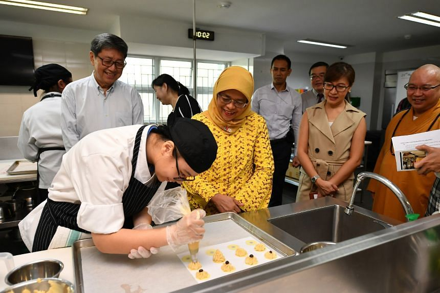 President Halimah Yacob looks on as Metta School student Jerica Tan Hui Min pipes chocolate chip cookies in the Baking Room.