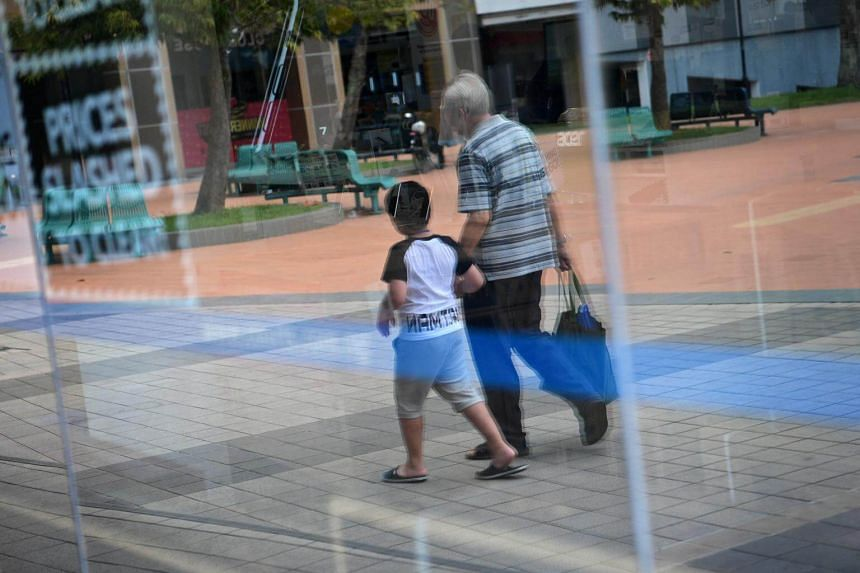 An elderly man walking hand-in-hand with his grandson at Toa Payoh, on March 14, 2017.