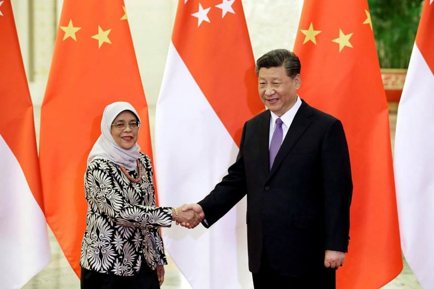 Singapore President Halimah Yacob and Chinese President Xi Jinping shake hands at the Great Hall of the People in Beijing, on May 14, 2019.