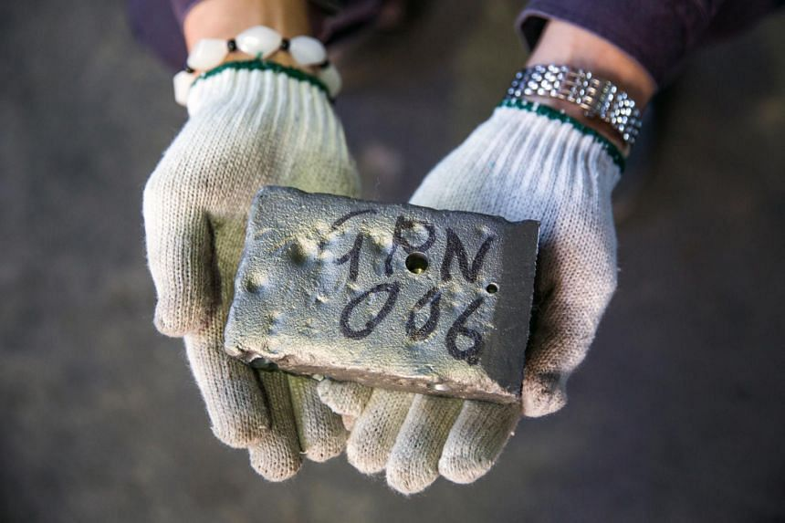 A worker holds an ingot of a rare earth metal used to make components for technology products at a factory in Tianjin, China, on Oct 16, 2013.
