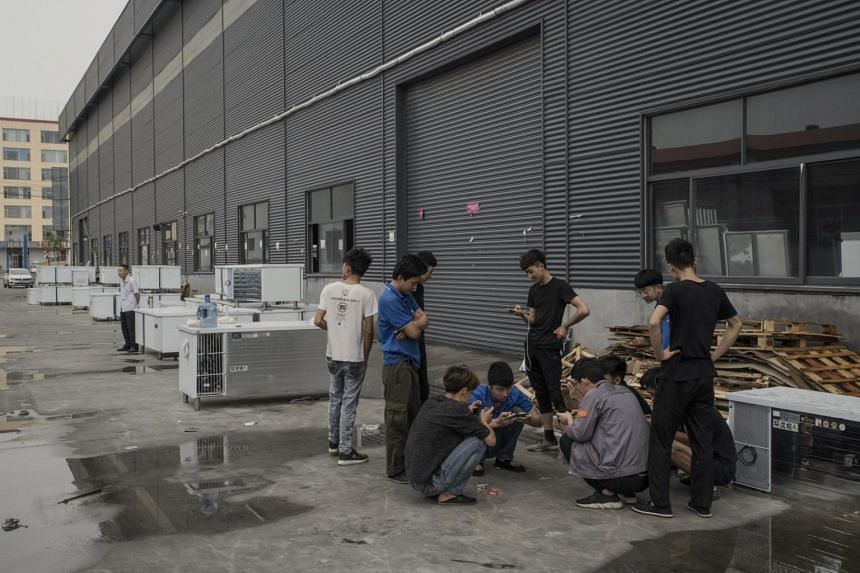 Workers play games on their phones outside a refrigerator factory in Xingfu, in the Shandong province of China.