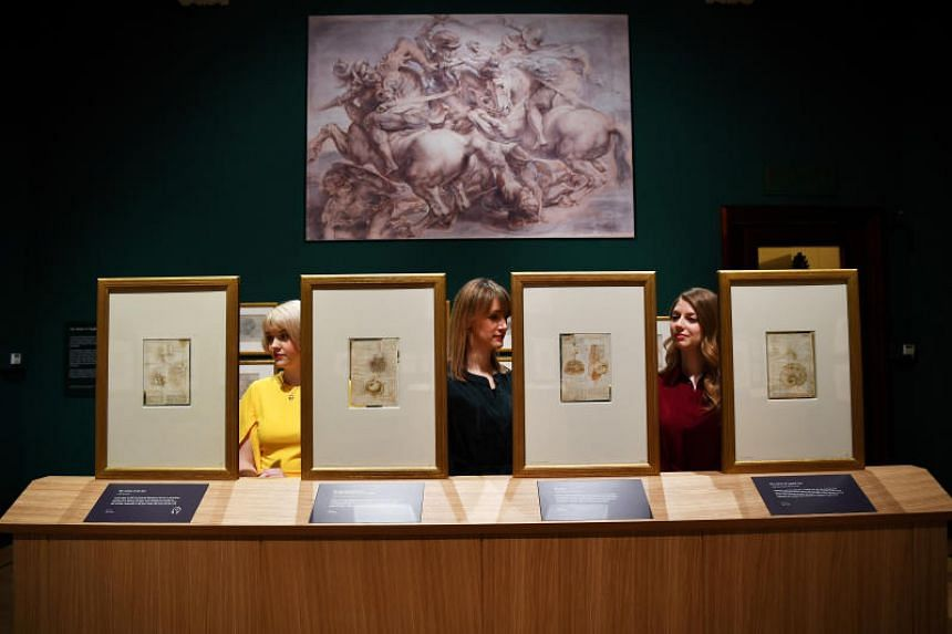 Royal Collection Trust staff pose beside some of Leonardo Da Vinci's anatomical studies at A Life in Drawing in London, on May 23, 2019.