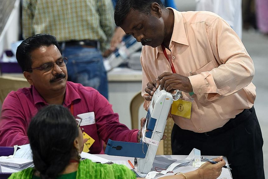 An Indian official inspecting an electronic voting machine during the ballot counting process at a booth in the Indian city of Mumbai yesterday. Prime Minister Narendra Modi returned to power on a wave of popularity, with his Bharatiya Janata Party p