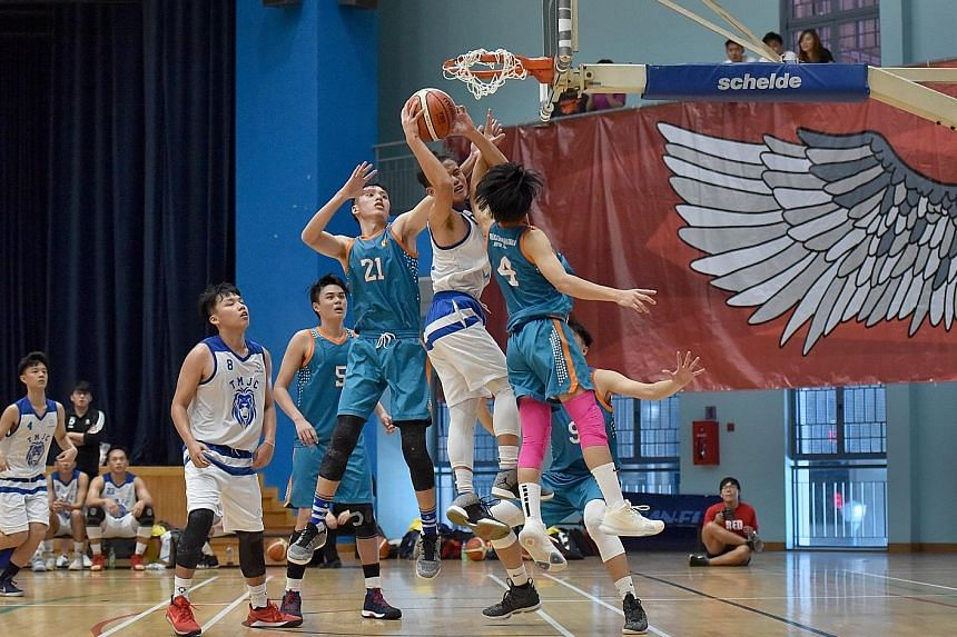 Tampines Meridian Junior College captain Tiong Chuan Yao attacking the rim despite being guarded closely by Anderson Serangoon Junior College's Louis Ho (right) and Keith Tan during their A Division final at the Jurong East Sports Hall yesterday. TMJ