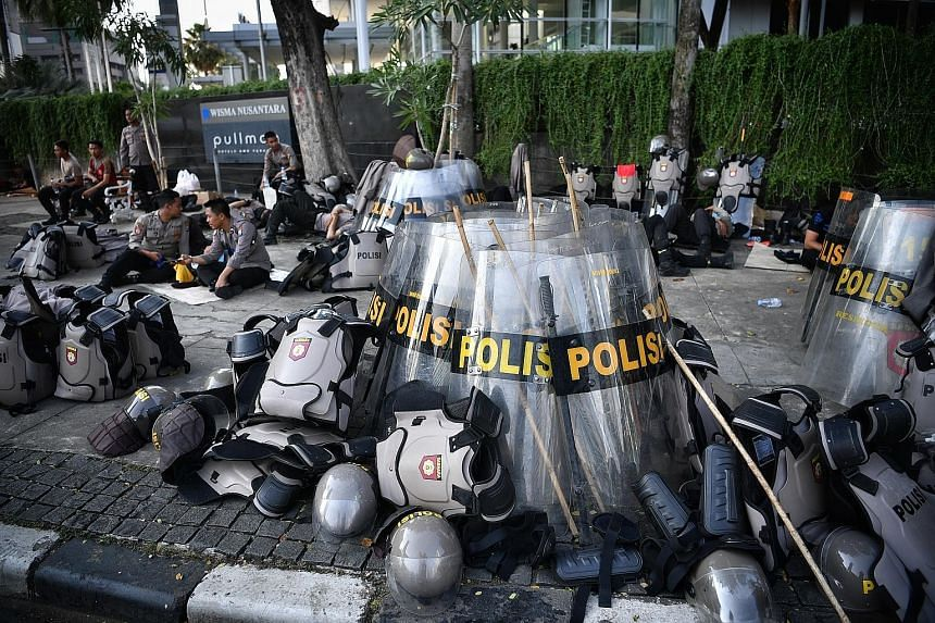 Right: Workers cleaning up debris yesterday after the previous night's violent clashes between police and rioters in Jakarta. Above: Police officers taking a breather. ST PHOTOS: ARIFFIN JAMAR