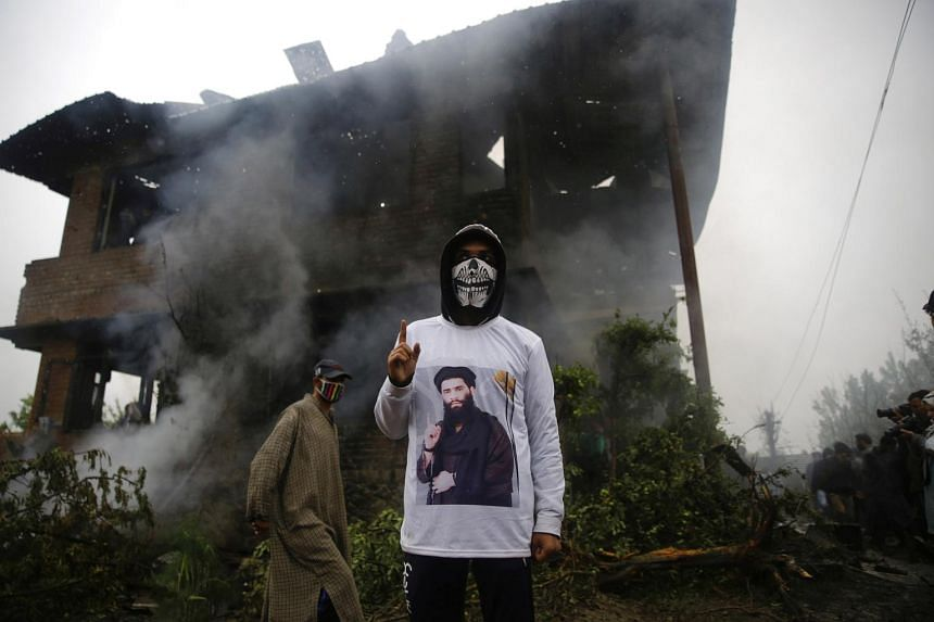 A Kashmiri youth wearing a shirt depicting a picture of militant commander Zakir Musa, as he stands inside of a damaged house where Musa was killed at Dadsara village in Tral, south of Srinagar, the summer capital of Indian Kashmir, on May 24, 2019.