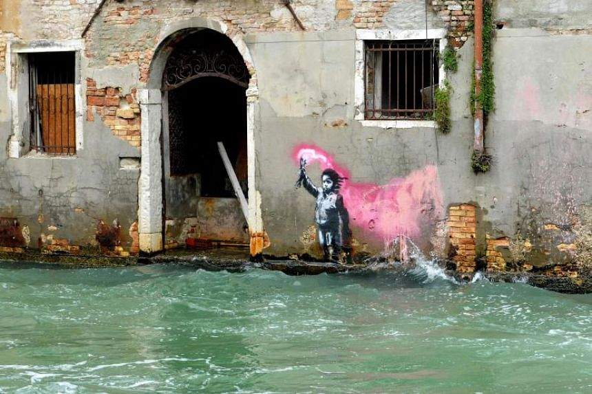An alleged work by British street artist Banksy is painted on the outer wall of a house overlooking the canal Rio de Ca Foscari, in Venice, on May 21, 2019.