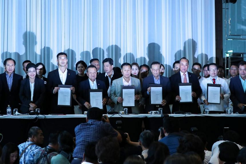 "Various Thai political party leaders hold up agreements during a news conference to form a ""democratic front"" in Bangkok, Thailand, on March 27, 2019."