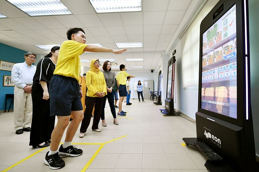 Metta School student Gabriel Choong Qing San, 17, learning how to shop in a supermarket using virtual reality software while being observed by President Halimah Yacob during her tour of the school yesterday. ST PHOTOS: LIM YAOHUI