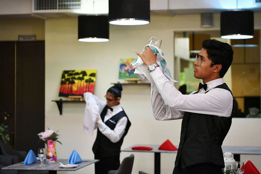 Student Muhammad Nur Haidar Haziq Nordin, 19, cleaning glassware at the school's cafe as part of his ITE skills certification course in hospitality services.