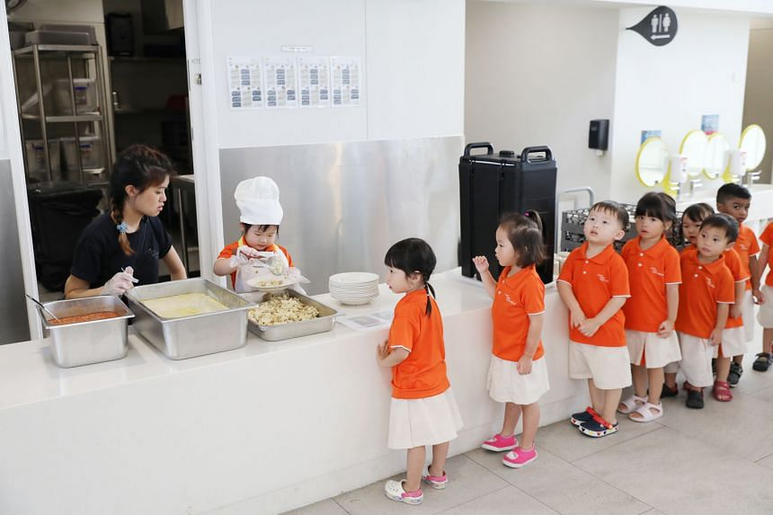 Children waiting to have their meals yesterday at My First Skool's first and largest early-years centre in Punggol Drive. The centre, which was officially opened yesterday, can take in up to 1,065 children and infants. It currently has more than 600