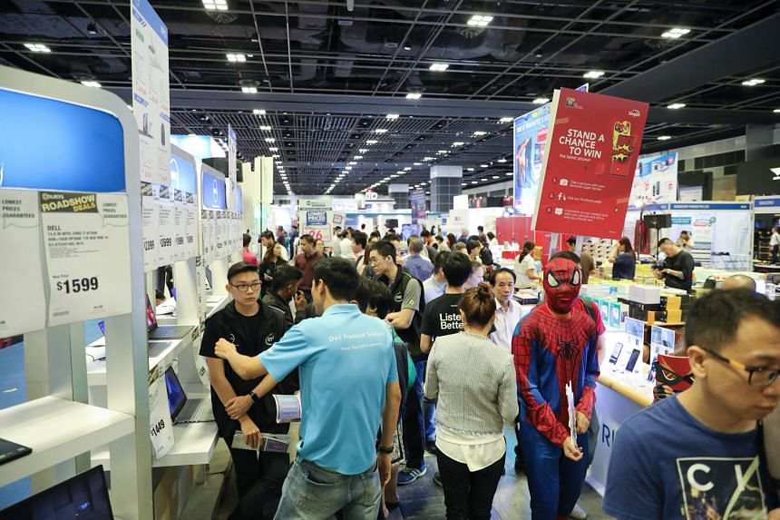 Visitors at the exhibition at the Suntec convention centre yesterday. A gadget trade-in initiative, a regular feature for visitors, has now been extended to corporate customers.
