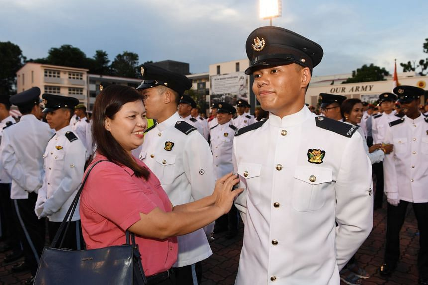 Third Sergeant Dela Cruz Carl Stephen Linao's mother affixing his rank to his uniform at the parade at Pasir Laba Camp. He was among the 1,000 cadets who graduated as full-fledged specialists yesterday.
