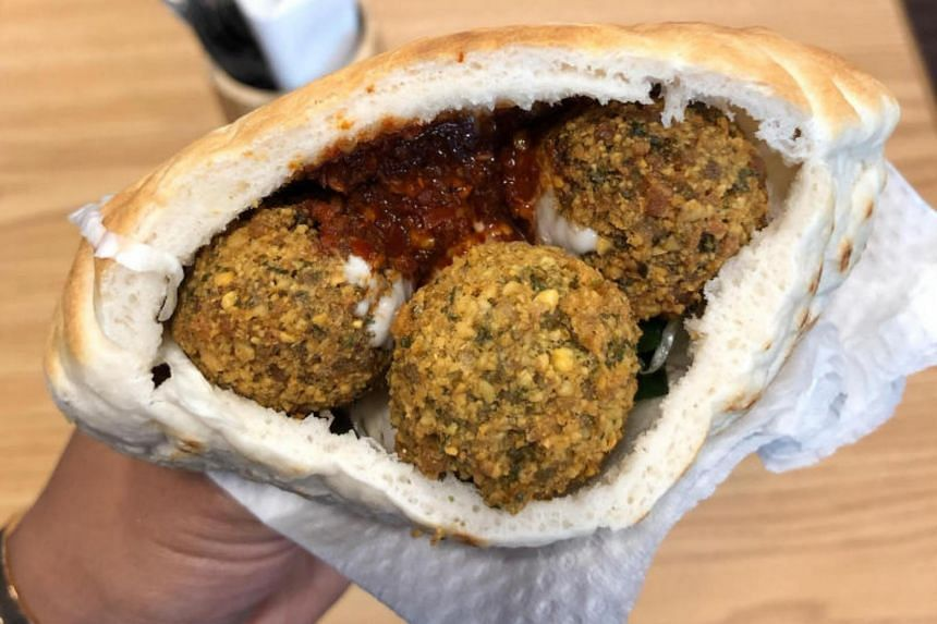 A pita pocket stuffed with falafel balls, a fresh salad and a sauerkraut-type pickled cabbage, as well as tahini and harissa.