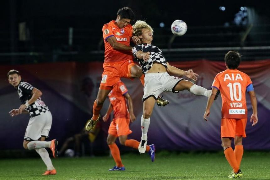 Albirex Niigata's Shuhei Sasahara (centre left) challenging Brunei DPMM's Blake Ricciuto for the ball during their Singapore Premier League match at Jurong East Stadium on May 24, 2019.
