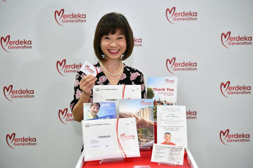 Senior Minister of State for Health Amy Khor with items inside a Merdeka Generation welcome folder.