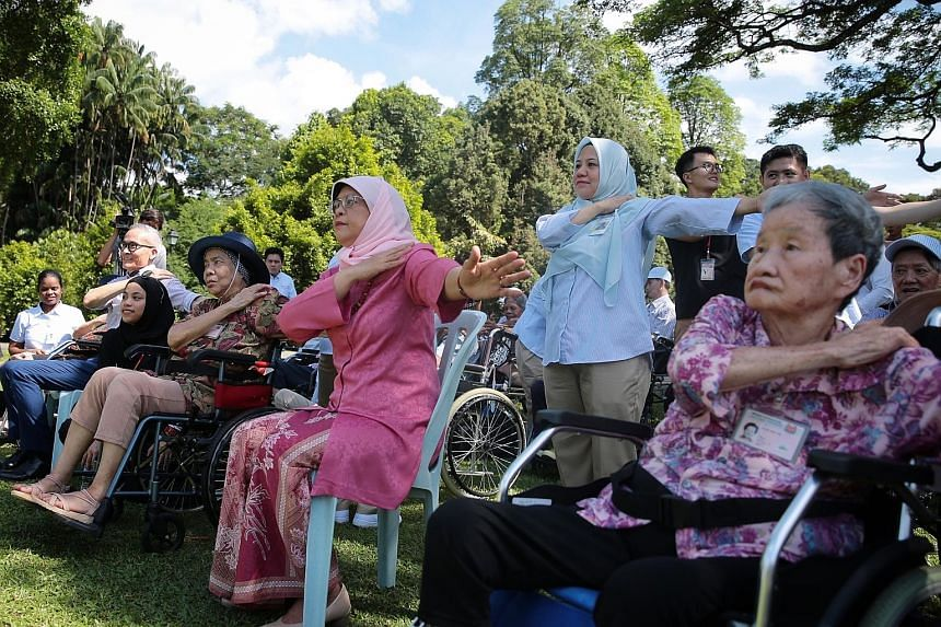 President Halimah Yacob doing wheelchair yoga with residents of the Thong Teck Home for Senior Citizens at the Istana yesterday.