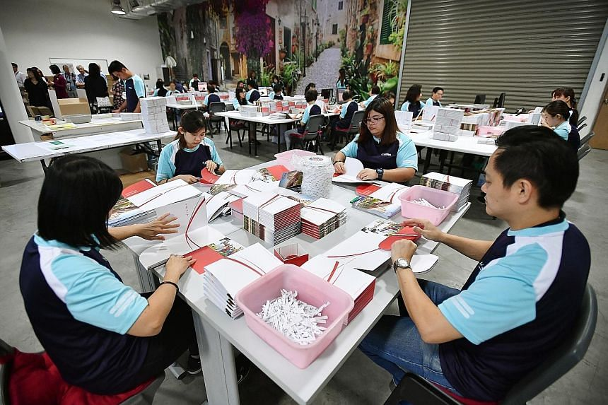 Medialink Printing Services staff (far right) preparing Merdeka Generation Package welcome folders, which will contain items such as (right) a member's card and thank-you letter from the Prime Minister. ST PHOTOS: LIM YAOHUI