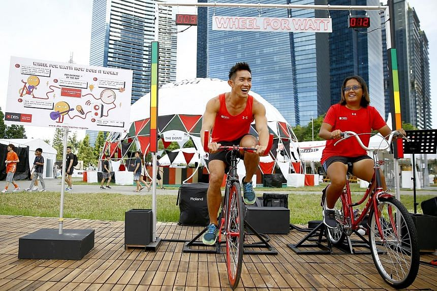 Kenneth Lee and Eveline Lau, captains of the DBS Asia Dragons men's and ladies' teams, cycling at the event's media preview yesterday. PHOTO: DBS