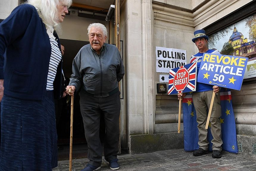 Voters leaving a polling station in London as an activist and Remain EU campaigner makes his stand outside. Britain voted in the European polls on Thursday, and the election continues on the continent this weekend, with results expected to start tric