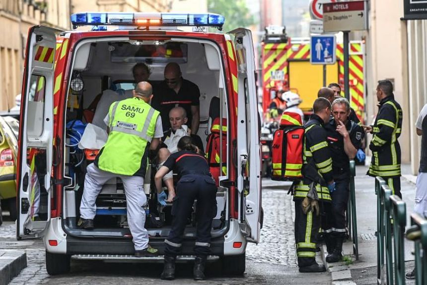 Emergency workers attended to an injured person in the back of an ambulance after a suspected package bomb blast along a pedestrian street in the heart of Lyon, southeast France, on May 24, 2019.