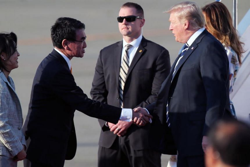 US President Donald Trump is greeted by Japanese Foreign Minister Taro Kono as he and US First Lady Melania Trump arrive at Haneda international Airport in Tokyo on May 25, 2019.