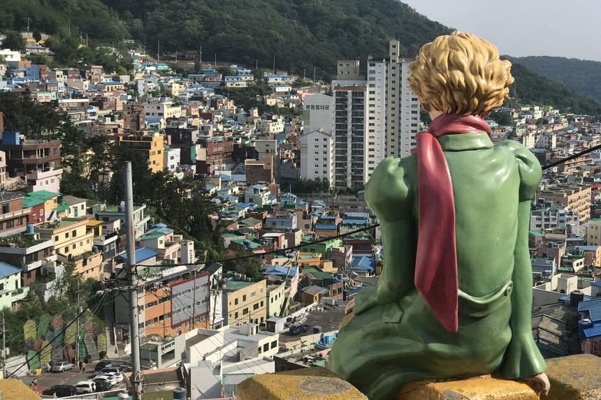 A statue of The Little Prince character from Antoine de Saint-Exupery's book, perched upon a guardrail at Gamcheon Cultural Village in Busan, South Korea.